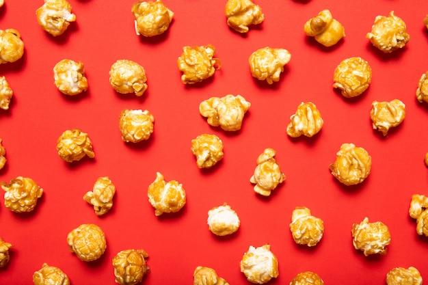 Вкусный попкорн на красном фоне. вид сверху