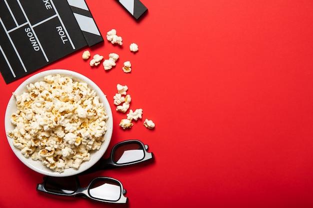 Тарелка с попкорном и кино клаппер на красном фоне. место для текста