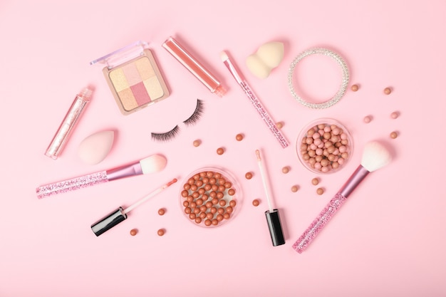 Набор декоративной косметики и аксессуаров на розовом фоне.