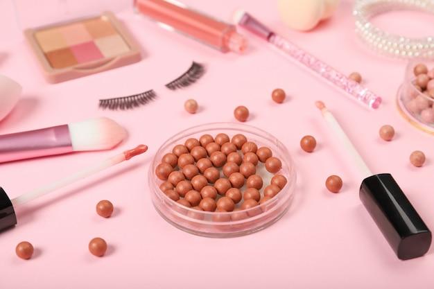 Мяч румянец и декоративная косметика на розовом фоне.