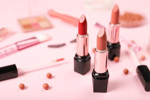 口紅とピンクの背景の化粧。テキストのための場所
