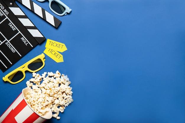 Бумажный стаканчик с попкорном и хлопушкой на синем фоне