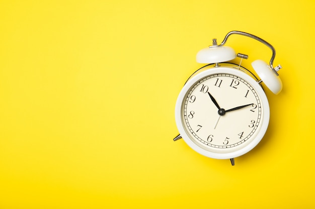 Белый будильник на желтом фоне