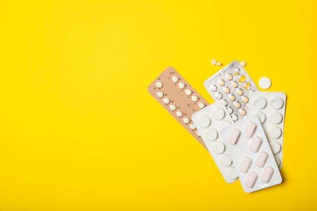 Противозачаточные таблетки на желтом фоне