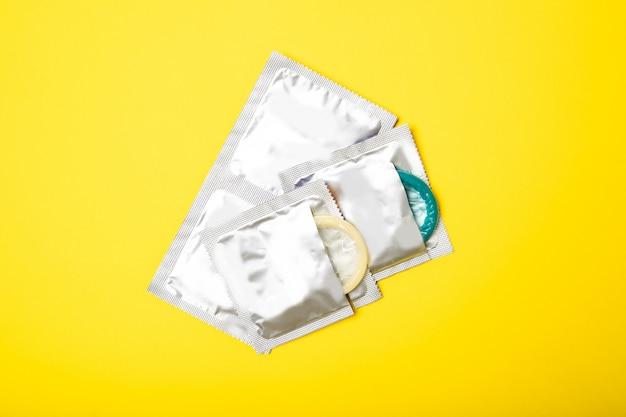 Презервативы в пакетах на желтом фоне