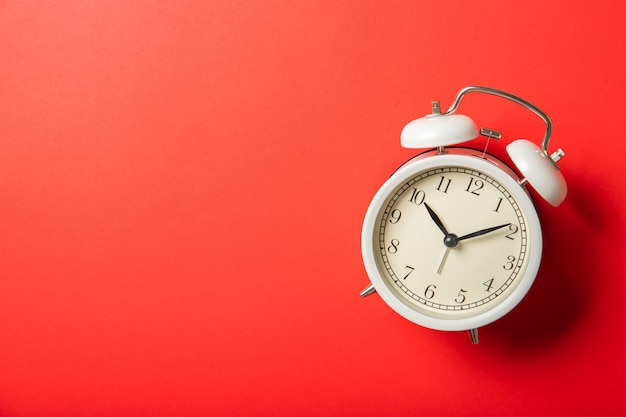 Белый будильник на красном фоне