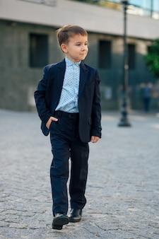 歩く古典的なダークブルーのビジネスコスチュームの少年