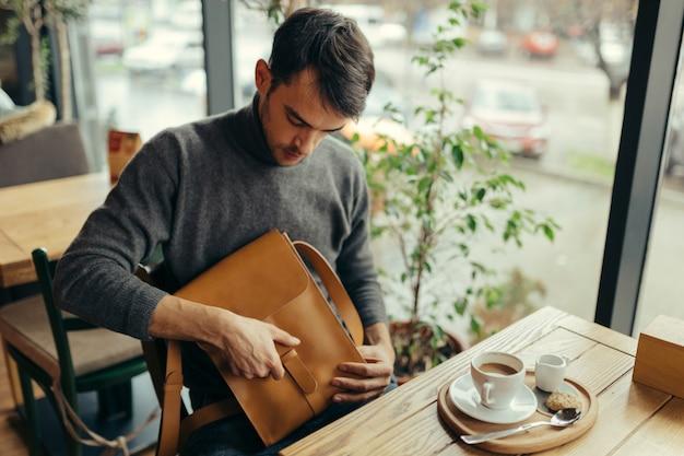 テーブルに座っている革のバッグを持つハンサムな実業家