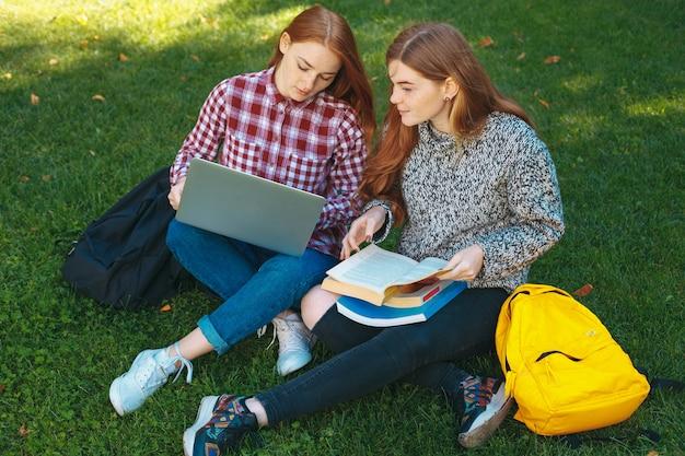 大学のキャンパスで屋外で勉強する学生