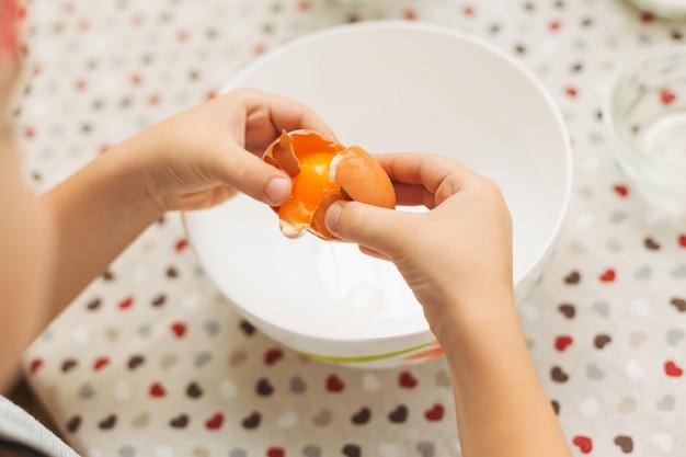 ボウルに卵を割るクローズアップ手