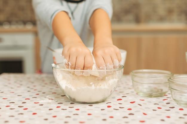 Руки ребенка крупным планом в стеклянной миске с мукой на кухне т