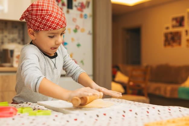 クリスマスのクッキーを焼く麺棒を持つ少年