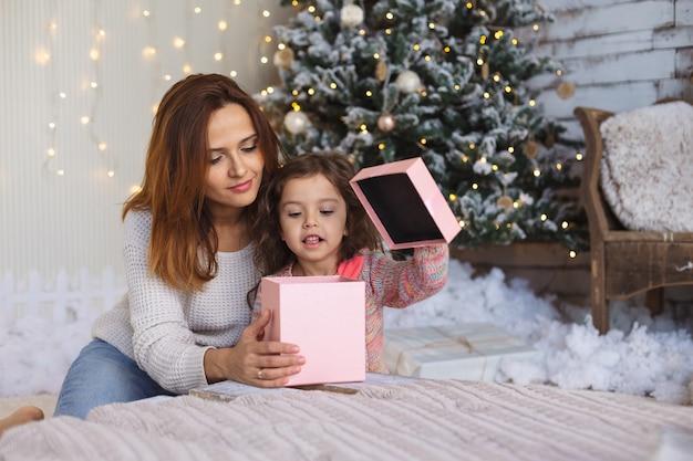 クリスマスギフトボックスの内側を見て子供と幸せなお母さん