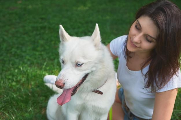青い目をした彼女の愛らしい白い犬を探している美しい女性