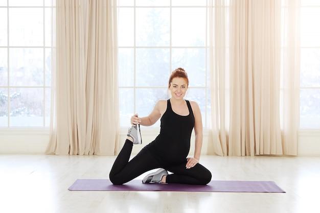 Молодая беременная йога женщина работает возле окна