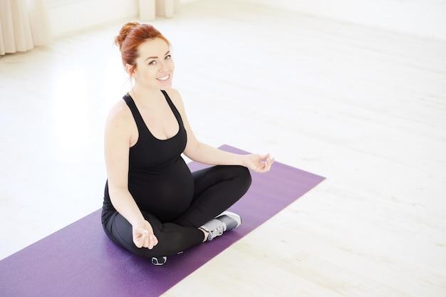 Усмехаясь беременная женщина йоги смотря и усмехаясь