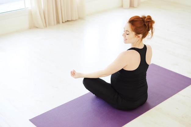 Улыбающаяся беременная женщина, сидящая в позе лотоса
