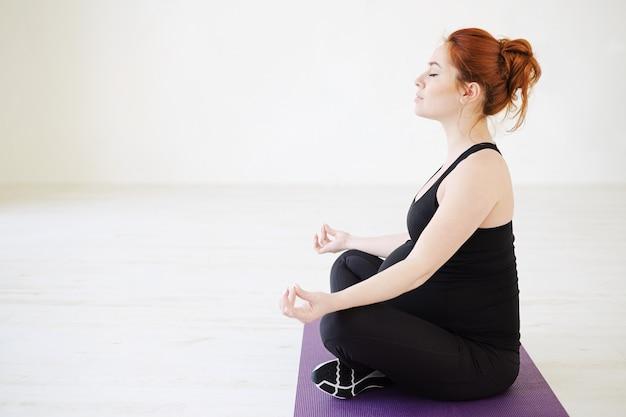 Беременная здоровая женщина медитирует с закрытыми глазами