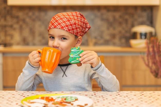 かわいい幸せな少年、お茶を飲んだり、クッキーを食べたり