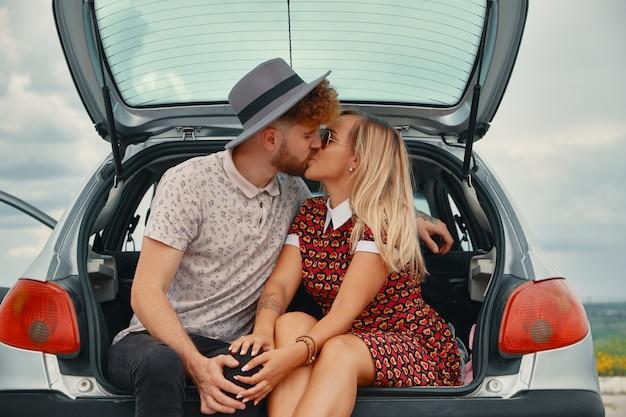 若い男と女が車のトランクでキス