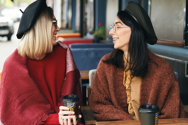 Портрет двух молодых женщин в кафе на открытом воздухе, пить кофе