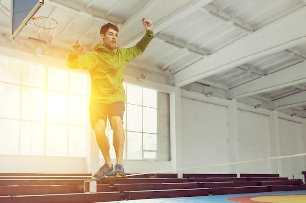 男はロープでスラックラインウォーキングとバランシング、スポーツホールでスラックライン
