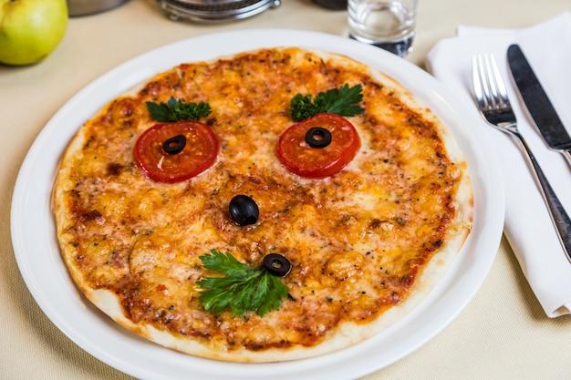 お子様メニューのレストラン料理-顔のピザ