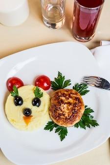 子メニュー-ジャガイモのピューレ、白い背景の上の顔を持つカツレツのレストラン料理