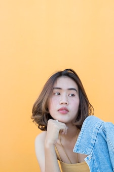 黄色の壁の背景に女性のポートレートスタイル