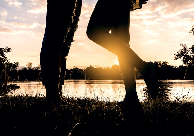 川の前に抱いて新婚夫婦の恋人にキスの夕日のシルエット