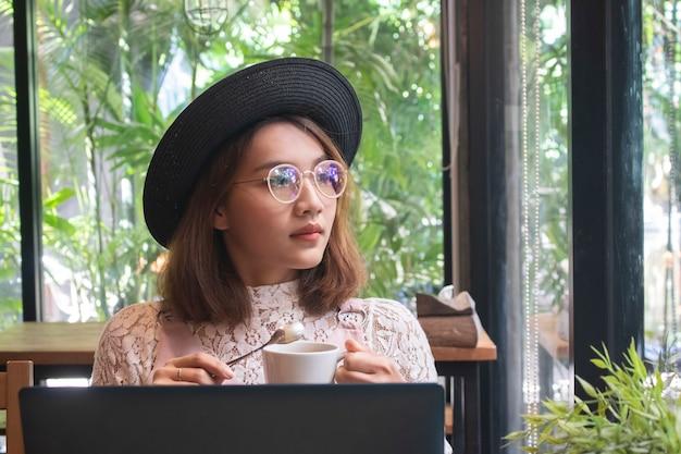 アジアの女性のコーヒーとカフェでのラップトップに取り組んで