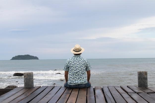 帽子を持つ若い女が一人でベンチに座る