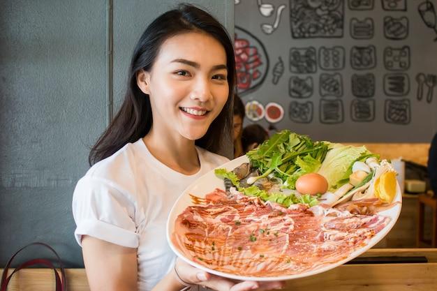 焼肉やしゃぶしゃぶ鍋のスライス牛肉の白いプレートを保持しているアジアの女性。