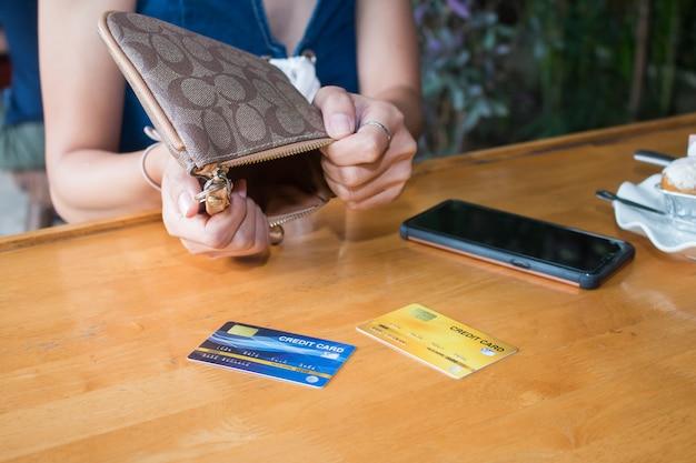 貧しいアジアの女性の手がお金を探して空の財布を開く