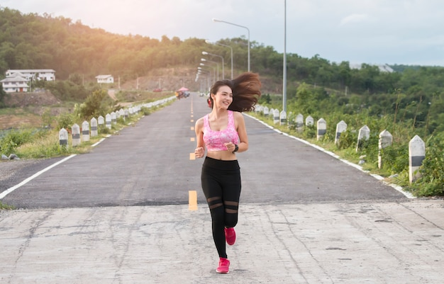 屋外を実行している幸せなアジア女性