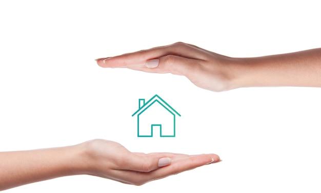 Концепция страхования жилья. фото руки, зависшие над иконой дома