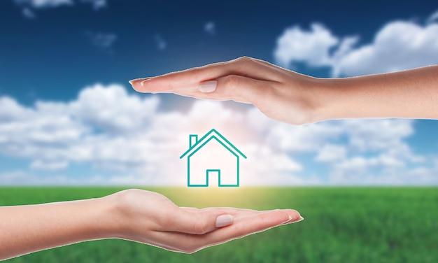 家の保険の概念。家のアイコンの上にホバリングする手の写真