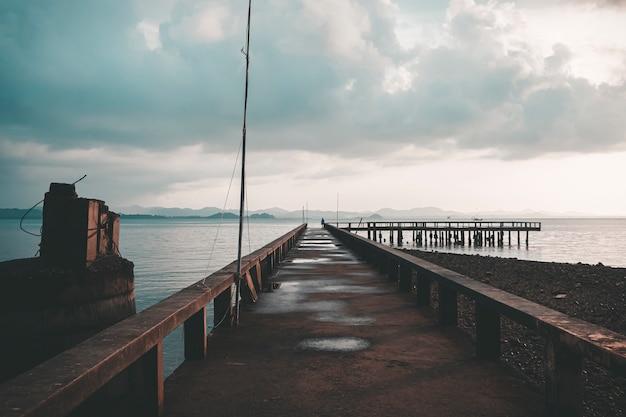 Конкретный прогулочный мост через море с облачным небом на пляже раваи