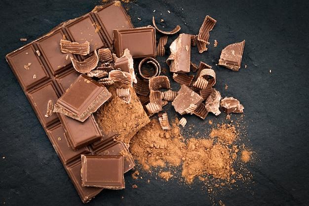 Разбитые кусочки шоколада и какао-порошок