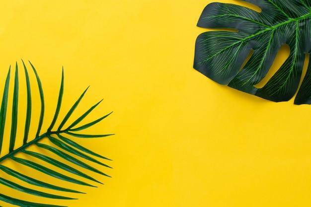 Плоские лежали зеленые листья пальмы на желтом фоне. концепция путешествия