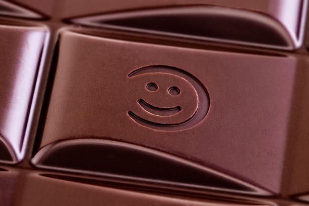 トップビューから笑顔でダークチョコレートバーのテクスチャ