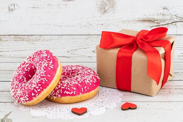 День святого валентина романтический завтрак. подарок, сердечки и пончики. день святого валентина концепция копировать пространство