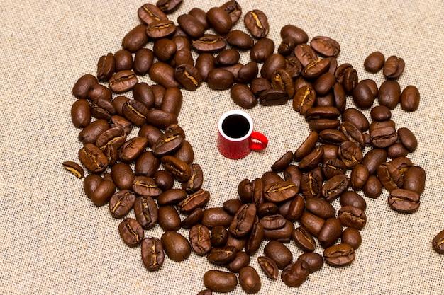 Сердце из кофейных зерен и чашка на мешковине