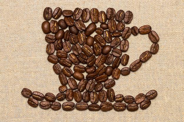 Жареные кофейные зерна помещены в форму чашки и блюдца на льняную поверхность