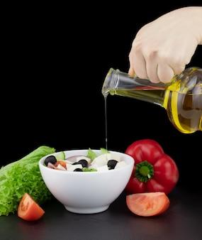 Овощной салат с оливковым маслом, льющимся из бутылки