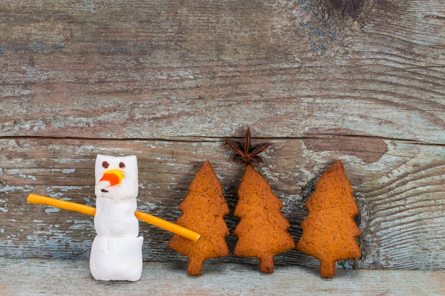 新年あけましておめでとうございますコンセプト面白いマシュマロ雪だるまと木製の背景にジンジャーブレッド