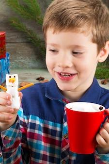Маленький мальчик с чашкой горячего шоколада с зефиром и снеговиком на фоне подарков, елки и елочных украшений