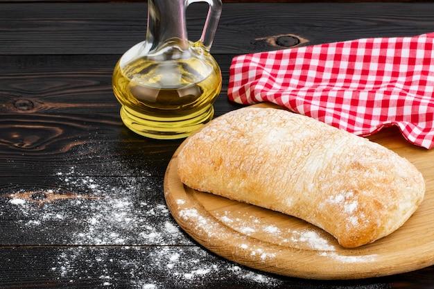 暗い木製のテーブルにまな板の上のチャバタのパンのパン