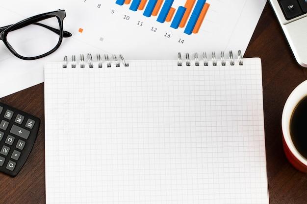 レポートを準備しています。青いグラフとチャート。ビジネスレポートと木製のテーブル上のドキュメントの山