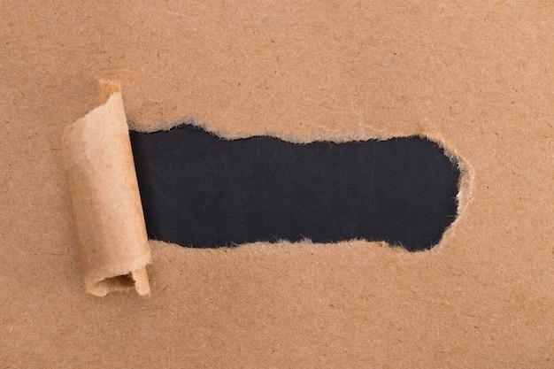 引き裂かれた側面を持つ茶色の紙の穴